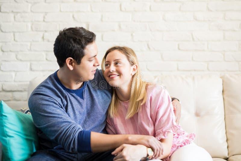 Giovani coppie amorose che si siedono sullo strato a casa fotografia stock
