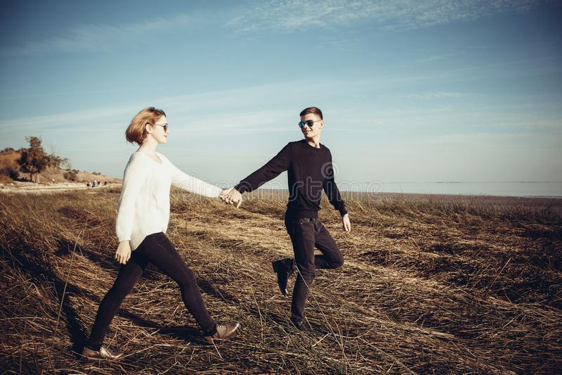 Giovani coppie amorose degli adolescenti, tenersi per mano di camminata sulla l fotografia stock