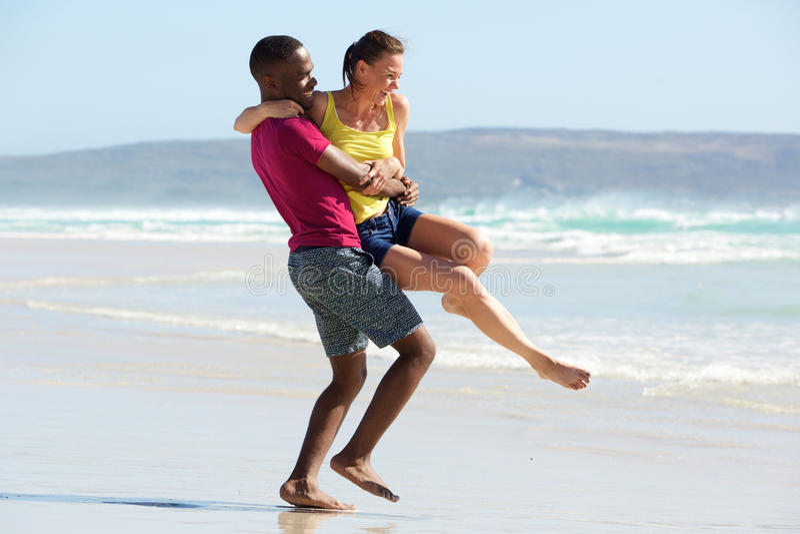 Giovani coppie amorose divertendosi sulla spiaggia immagine stock libera da diritti