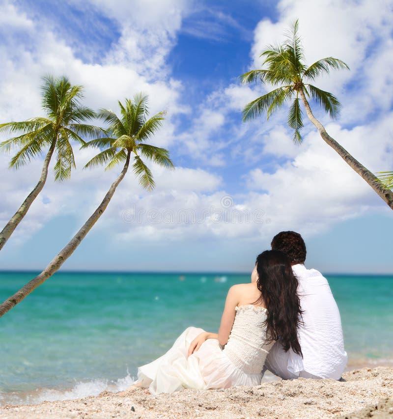 Giovani coppie amorose sul fondo tropicale del mare fotografia stock libera da diritti