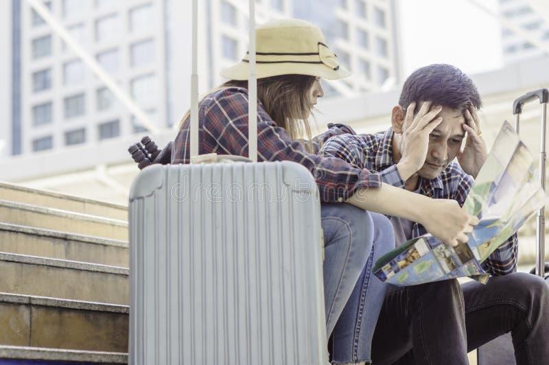 Giovani coppie asiatiche dei viaggiatori, sguardo alla mappa e sforzo perché fotografia stock libera da diritti