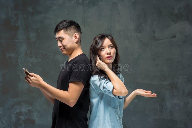 Giovani coppie asiatiche facendo uso del cellulare, ritratto del primo piano fotografia stock