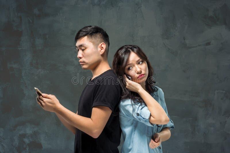 Giovani coppie asiatiche facendo uso del cellulare, ritratto del primo piano immagine stock libera da diritti
