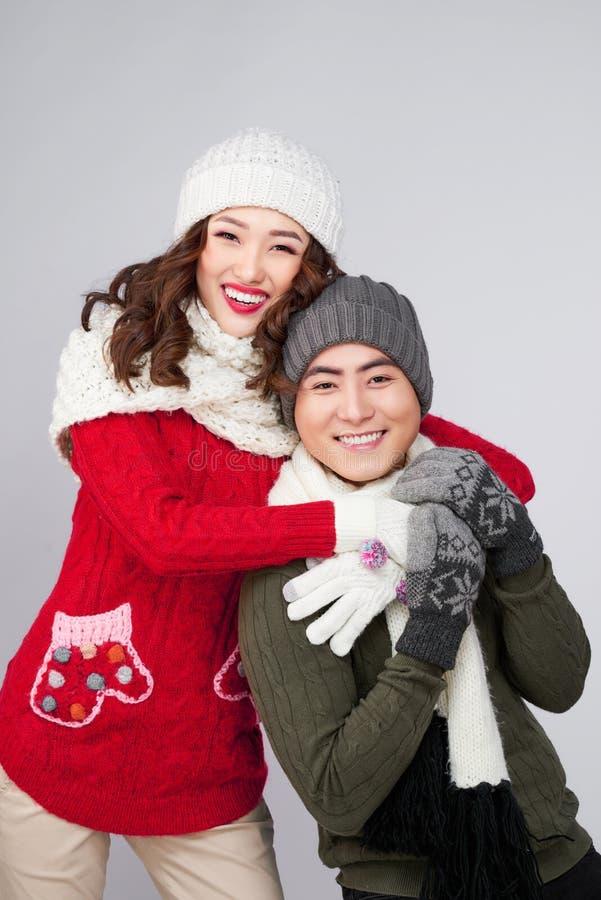 Giovani coppie asiatiche felici che portano sciarpa calda tricottata, sopra la b grigia fotografia stock