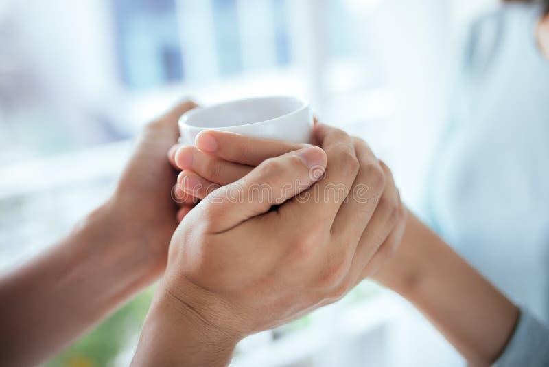 Giovani coppie asiatiche pacifiche che si rilassano a casa con la tazza di tè fotografie stock