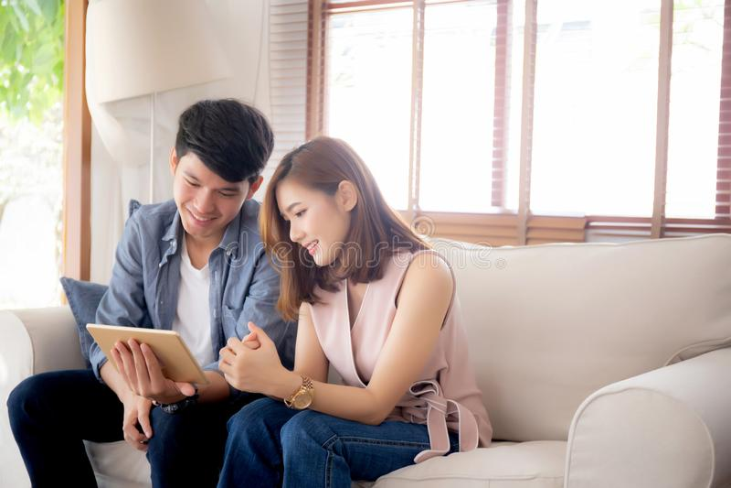 Giovani coppie asiatiche rilassarsi guardando spettacolo della compressa su Internet insieme sul sof? a casa fotografia stock