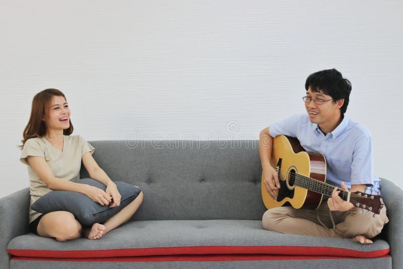Giovani coppie asiatiche rilassate che giocano insieme chitarra acustica nel salone Concetto della gente di romance e di amore fotografia stock