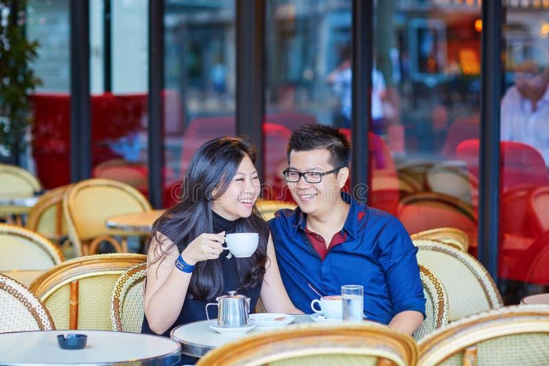 Giovani coppie asiatiche romantiche in caffè parigino fotografia stock