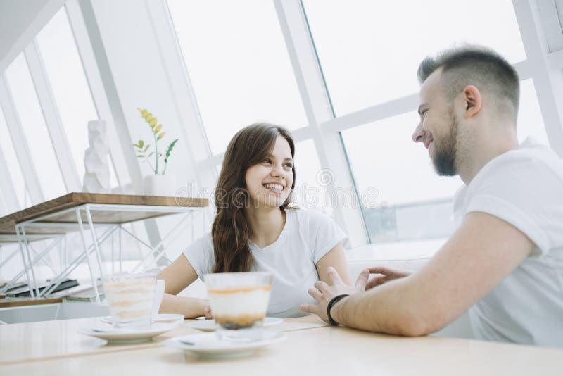 Giovani coppie attraenti ad una data in un caffè immagine stock
