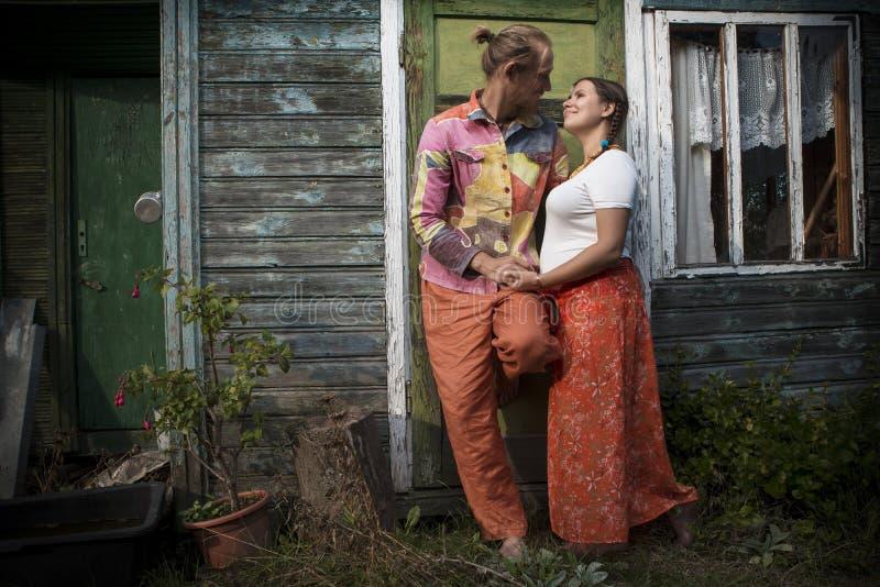 Giovani coppie attraenti alla casa di legno fotografia stock libera da diritti