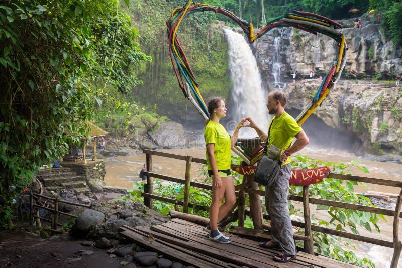 Giovani coppie attraenti che baciano sotto la cascata della giungla fotografia stock libera da diritti