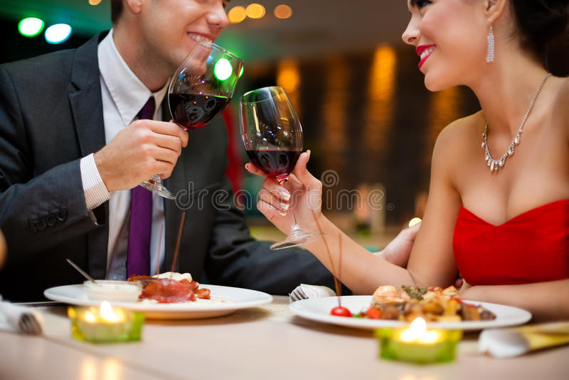 Giovani coppie attraenti che bevono vino rosso in ristorante immagine stock