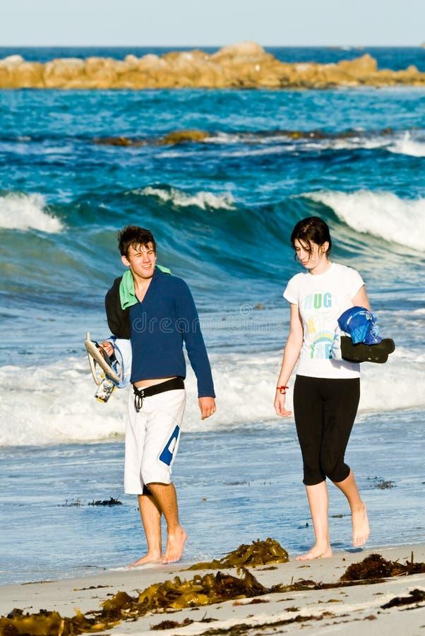 Giovani coppie attraenti che camminano sulla spiaggia immagine stock