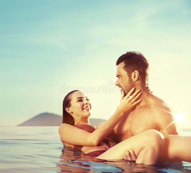 Giovani, coppie attraenti che si rilassano in uno stagno caldo e tropicale fotografie stock