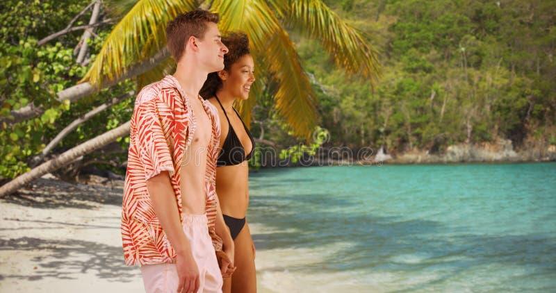 Giovani coppie attraenti che si tengono per mano sulla spiaggia tropicale fotografia stock