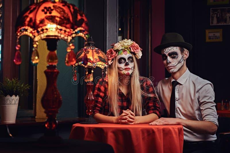 Giovani coppie attraenti con trucco del non morto durante la datazione ad un ristorante messicano fotografia stock