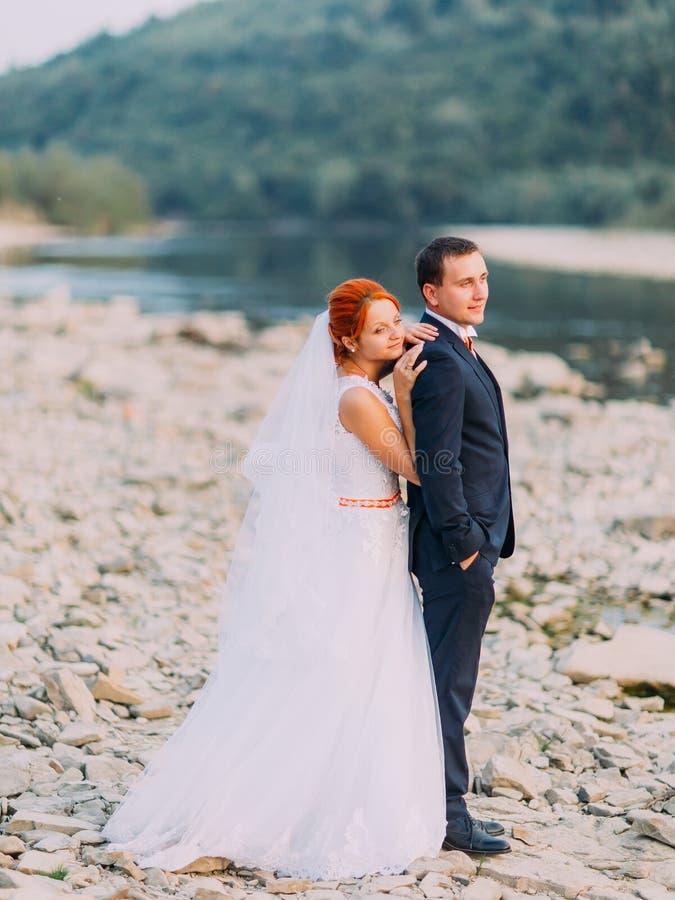 Giovani coppie attraenti di nozze Riva di un fiume della montagna con le pietre su fondo fotografia stock libera da diritti