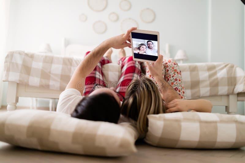 Giovani coppie attraenti facendo uso della compressa in camera da letto fotografia stock