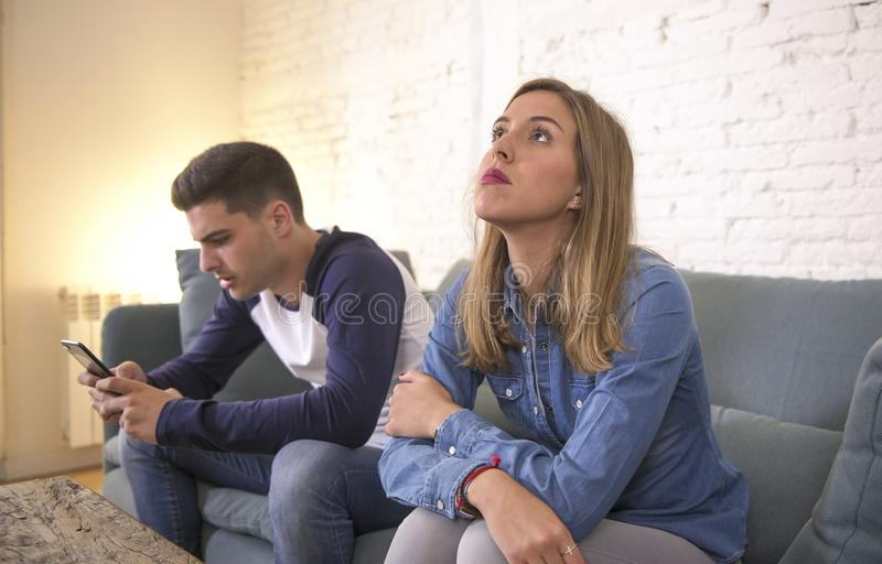 Giovani coppie attraenti nel problema di relazione con il ragazzo di dipendenza del telefono cellulare di Internet che trascura t fotografie stock