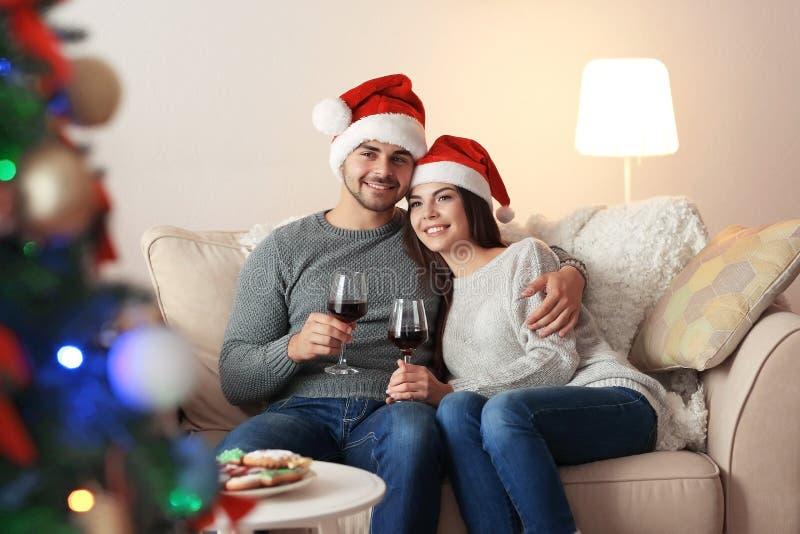 Giovani coppie in cappelli di Santa Claus che bevono vino immagine stock libera da diritti