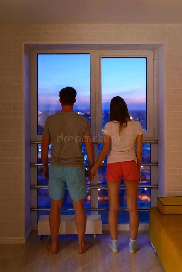 Giovani coppie a casa che esaminano il panorama di sera della città attraverso la finestra immagini stock libere da diritti