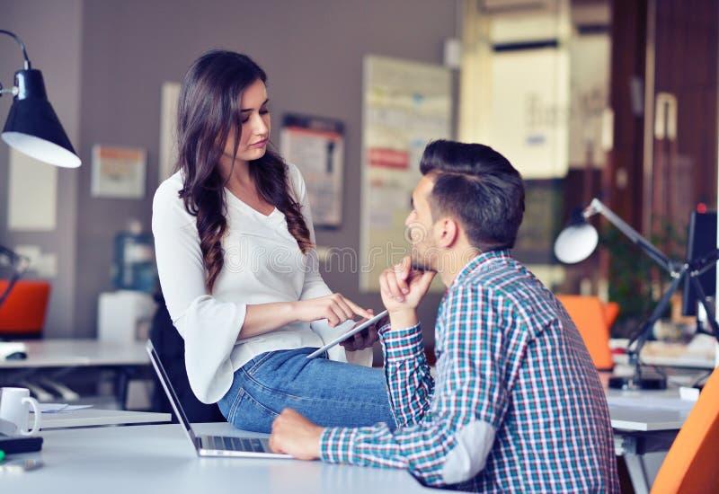 Giovani coppie casuali di affari facendo uso del computer nell'ufficio Coworking, responsabile creativo che mostra nuova idea sta fotografie stock