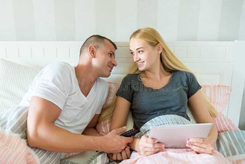 Giovani coppie caucasiche attraenti a letto La donna che tiene la compressa digitale, equipaggia amoroso l'esame lei, sperando di fotografia stock