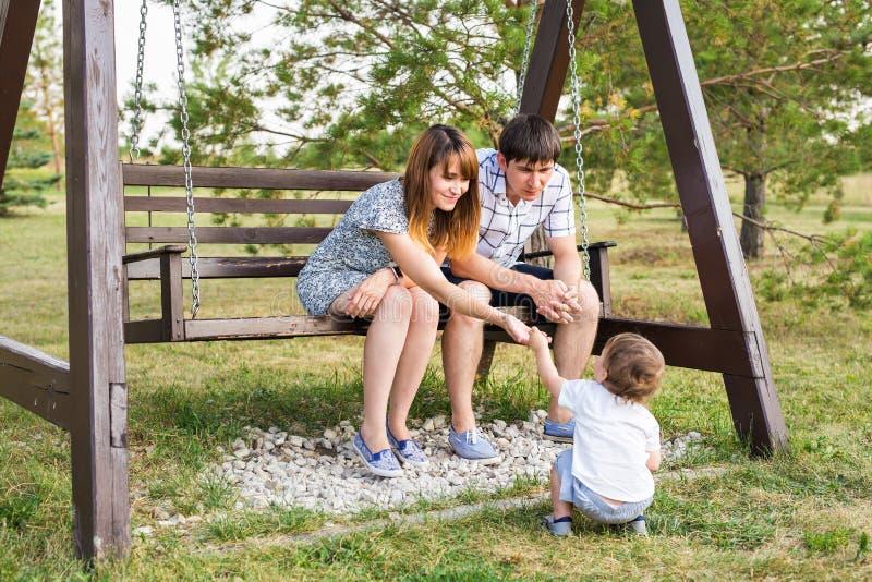 Giovani coppie caucasiche felici con il neonato Genitori e figlio divertendosi insieme Gioco del padre e della madre con il bambi immagine stock libera da diritti