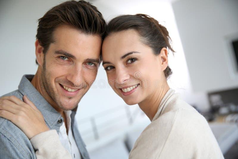 Giovani coppie che abbracciano a casa fotografia stock