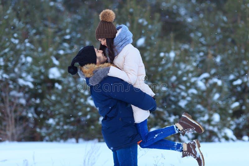 Giovani coppie che abbracciano e che baciano nella foresta di inverno immagine stock libera da diritti