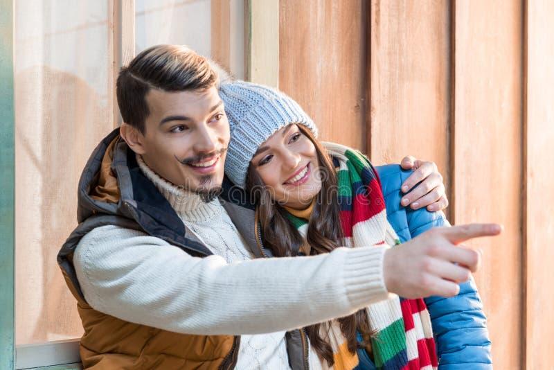 Giovani coppie che abbracciano e che indicano via con il dito sul portico fotografie stock