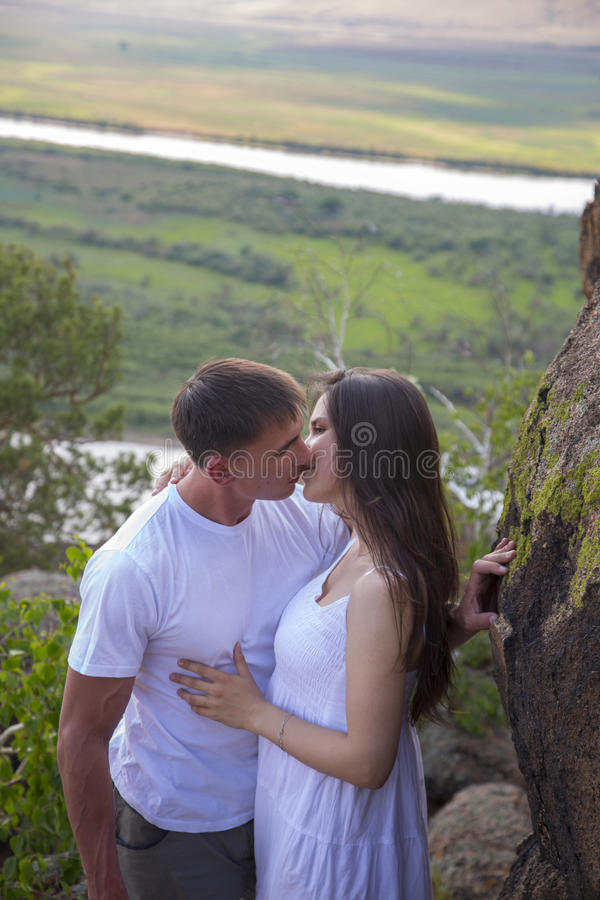 Giovani coppie che abbracciano in montagne immagine stock libera da diritti
