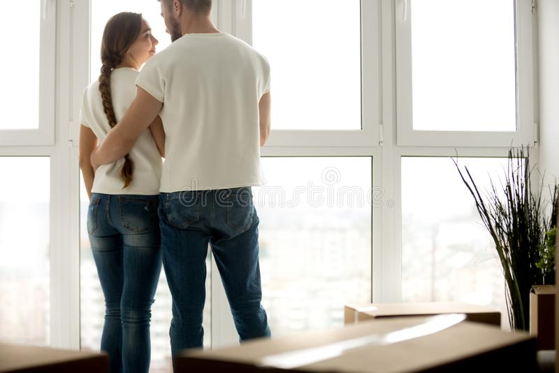 Giovani coppie che abbracciano in nuovo appartamento con gli effetti personali imballati fotografia stock