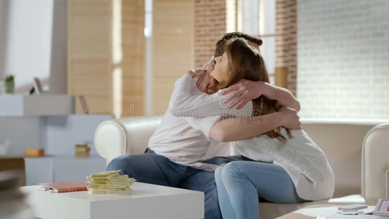 Giovani coppie che abbracciano strettamente, eccitato circa il profitto di gran affare, soldi sulla tavola immagine stock libera da diritti