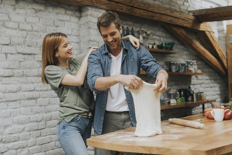Giovani coppie che agglutinano insieme pizza in cucina immagine stock