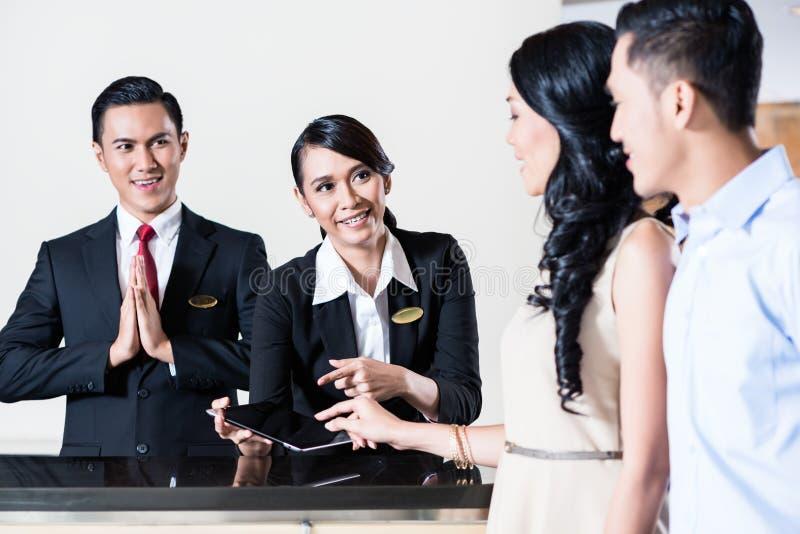 Giovani coppie che arrivano all'area reception dell'hotel fotografia stock libera da diritti
