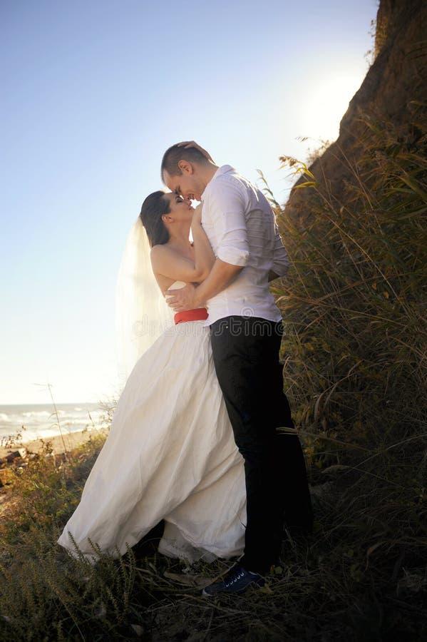 Giovani coppie che baciano in abito di nozze, all'aperto fotografia stock libera da diritti