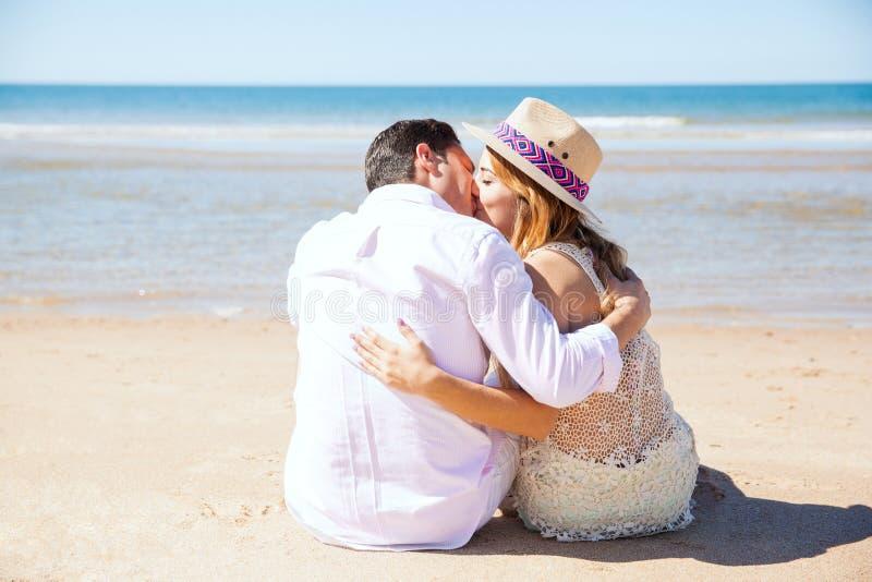 Giovani coppie che baciano alla spiaggia immagini stock libere da diritti