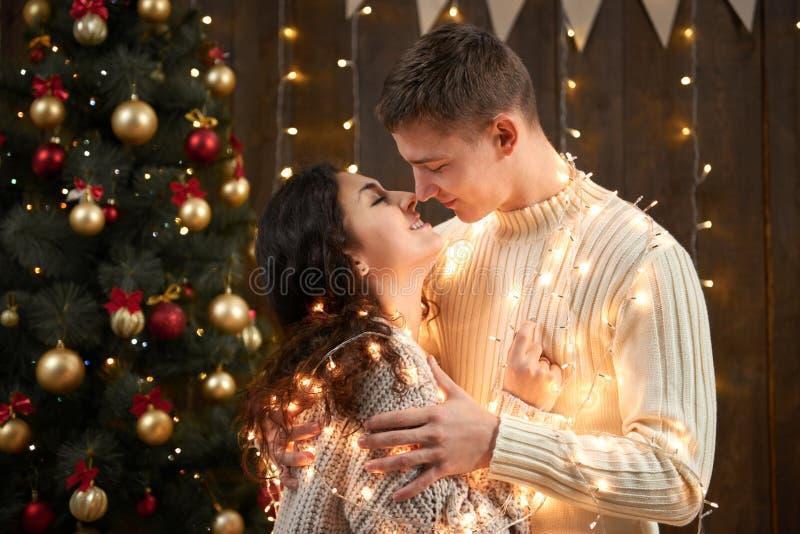 Giovani coppie che baciano alle luci ed alla decorazione di natale, vestite nel bianco, albero di abete su fondo di legno scuro,  fotografia stock