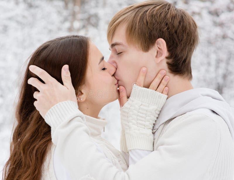 Giovani coppie che baciano nella foresta di inverno fotografia stock libera da diritti