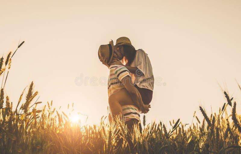 Giovani coppie che baciano sui precedenti di un tramonto nel giacimento di grano immagine stock libera da diritti