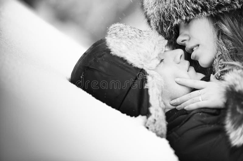 Giovani coppie che baciano sulla neve fotografia stock libera da diritti