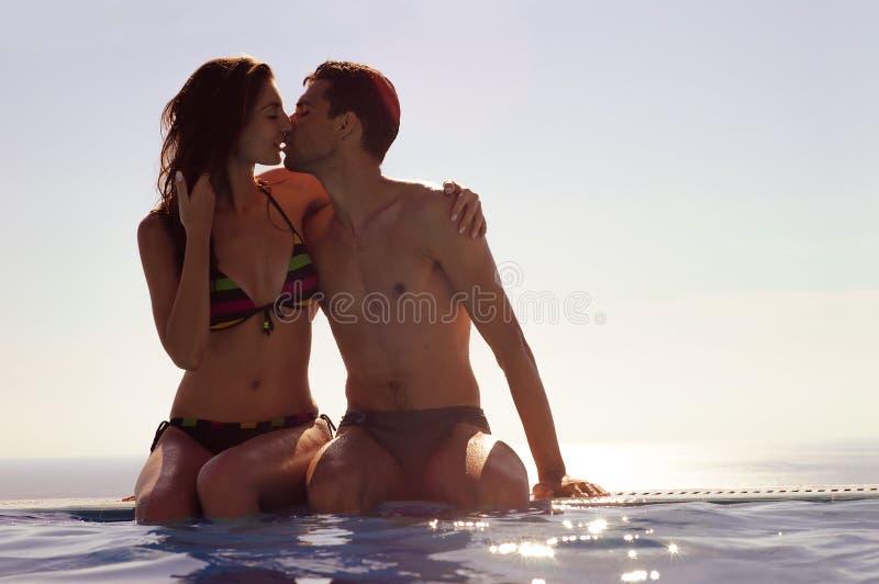 Giovani coppie che baciano in una piscina di infinito Coppie di luna di miele alla località di soggiorno di lusso vacanza romanti immagini stock