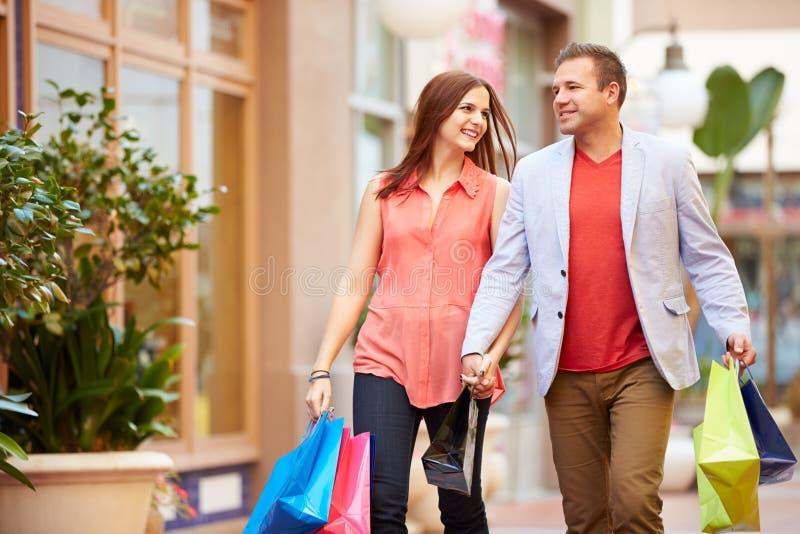 Giovani coppie che camminano attraverso il centro commerciale con i sacchetti della spesa fotografia stock