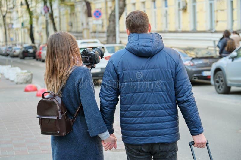 Giovani coppie che camminano intorno alla città con la valigia della macchina fotografica, vista dalla parte posteriore, gioventù immagine stock