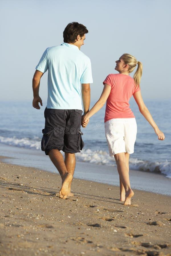 Giovani coppie che camminano lungo la spiaggia fotografia stock libera da diritti