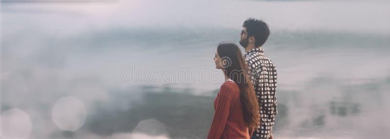Giovani coppie che camminano sulla spiaggia fotografia stock libera da diritti