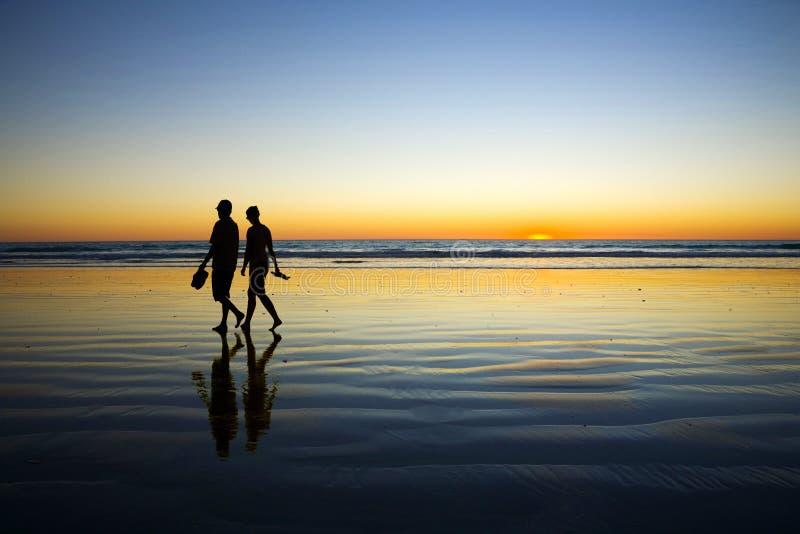 Giovani coppie che camminano sulla spiaggia romantica al tramonto fotografie stock libere da diritti