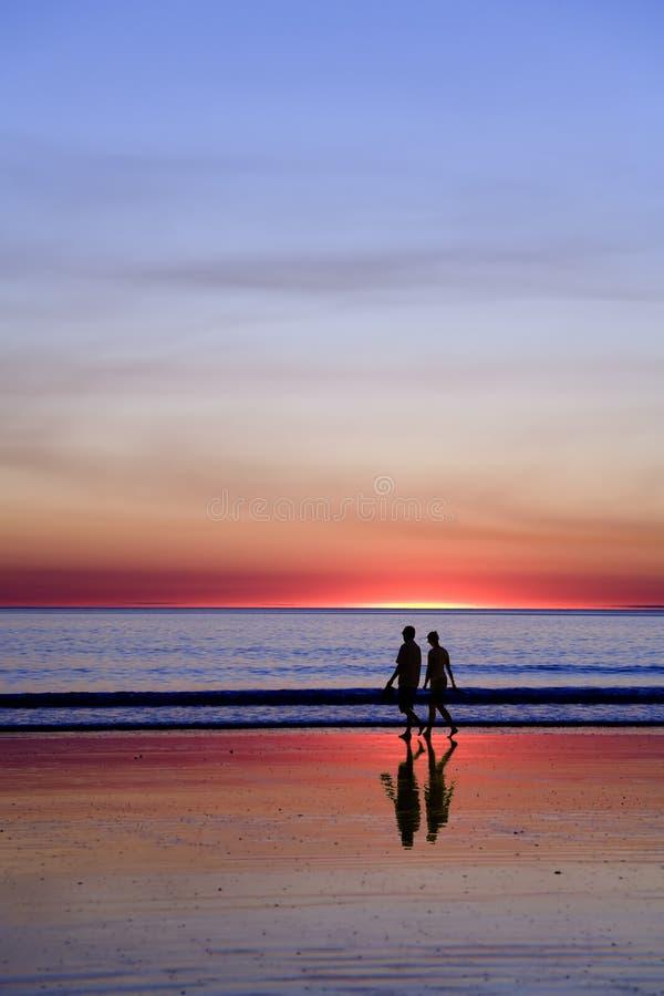 Giovani coppie che camminano sulla spiaggia romantica al tramonto fotografia stock libera da diritti