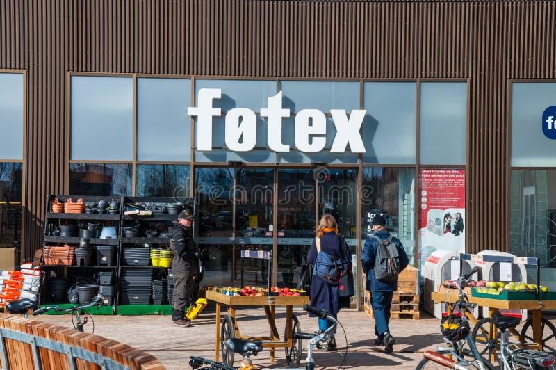 Giovani coppie che camminano verso un supermercato e un senzatetto che vende un giornale fotografie stock